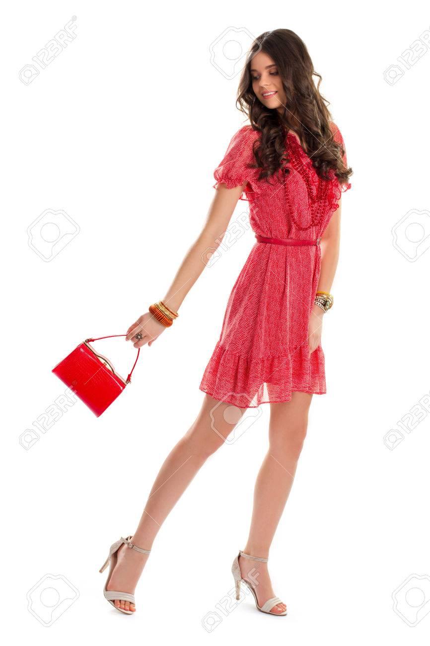 mädchen im roten kleid lächelnd. rote handtasche und beige fersen. jung und  hübsch. stilvolle kleidung aus neuen kollektion.