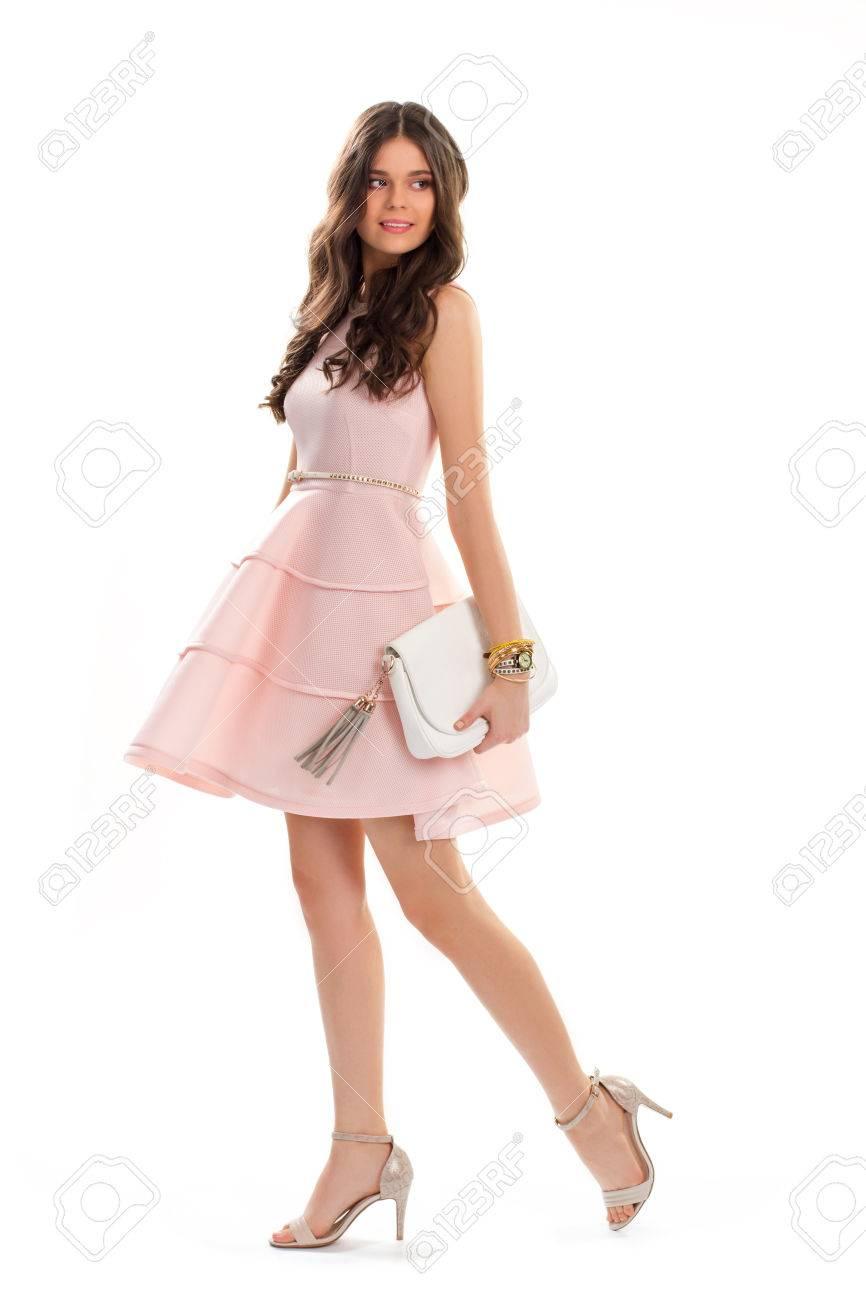 promo code e131d a7b00 Donna in abito corto di salmone. La ragazza attraente è sorridente. Abito  senza maniche con pieghe. Il giovane modello indossa abiti da sera.
