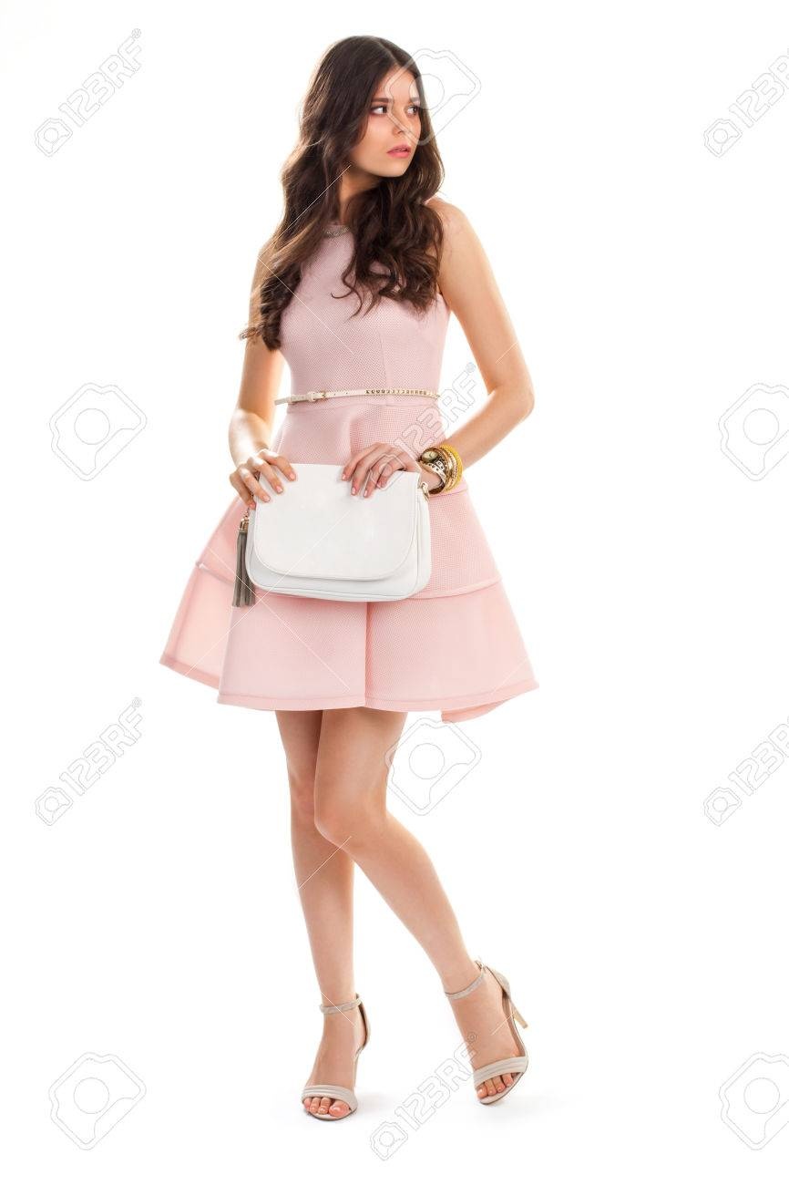 5f55e622a Foto de archivo - La mujer joven lleva el vestido de color salmón. Zapatos  de tacón y bolso blanco. Nueva ropa de moda. Vestido de algodón y cinturón  de ...