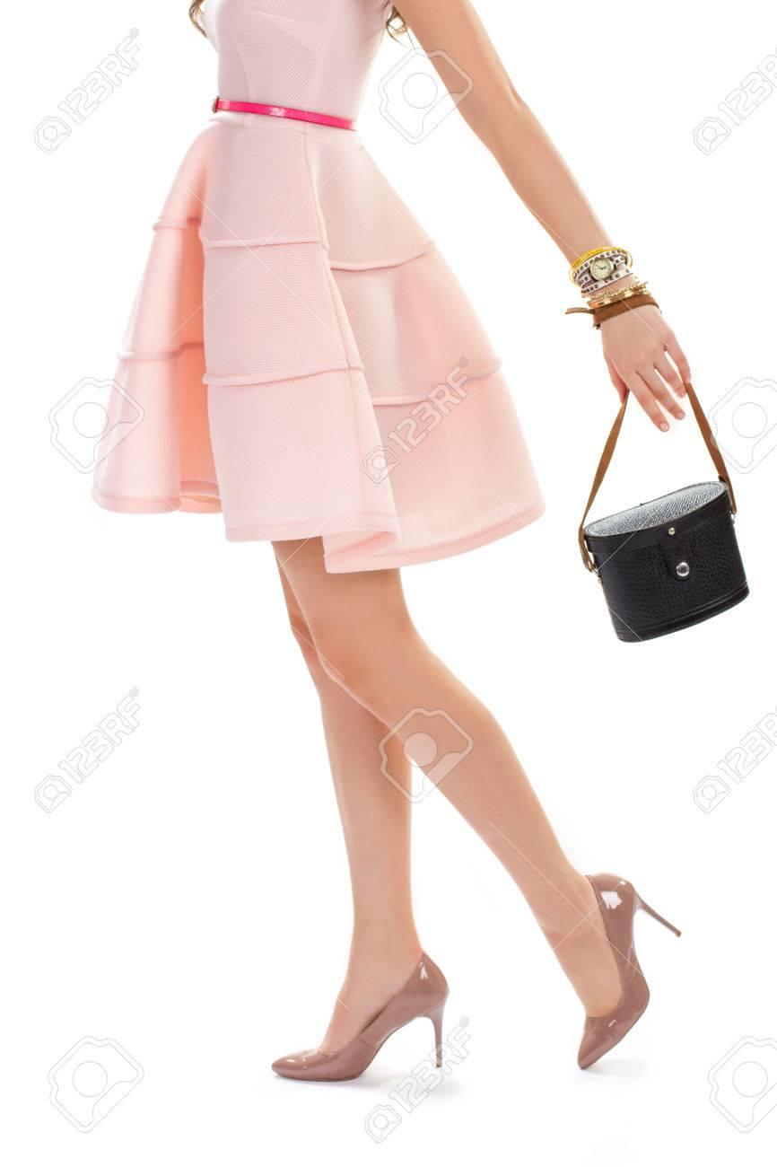 76f242b3e6 Foto de archivo - La mujer en zapatos de tacón brillantes. vestido de salmón  con cinta de colores. bolso de cuero de la vendimia y reloj. traje de  primavera ...