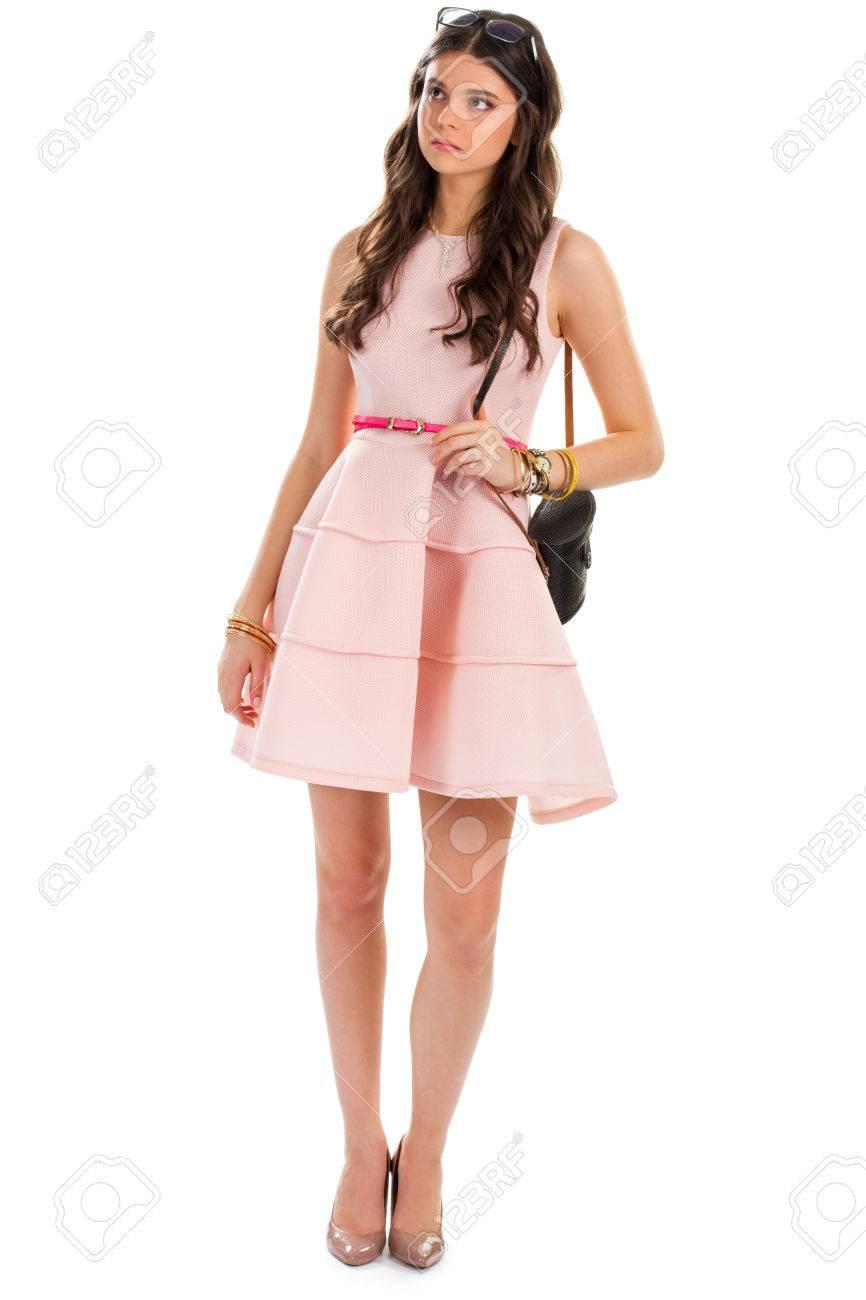 c8dc6cd397 Foto de archivo - La mujer en zapatos de tacón. vestido corto con cinturón  de color rosa. niña sorprendida en el fondo blanco. La duda y la vacilación.