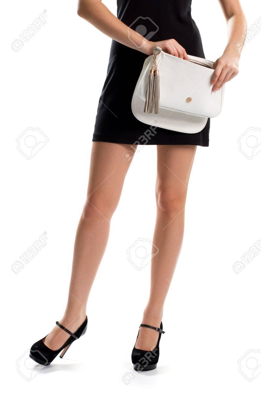 Señora en tacones negros. Manos de la mujer bolsa blanca abierta. calzado de ante y bolso de cuero. Nuevo accesorio de la famosa marca.