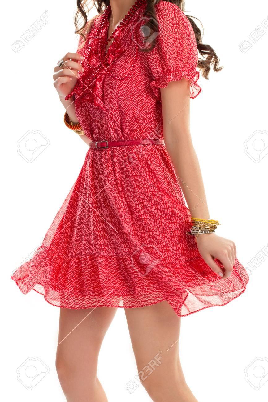 frau in gepunktetes kleid. rotes kleid mit zerknitterten Ärmeln. dünne  armbänder und schmaler gürtel. sommer-look für mädchen.