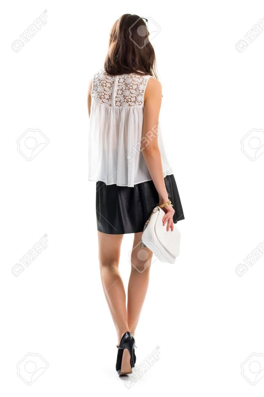 Foto de archivo - La chica joven desgasta la falda corta. Bolso blanco y  negro zapatos de tacón. equipo de la tarde agradable con los accesorios.  pulseras ... cab88ff95424