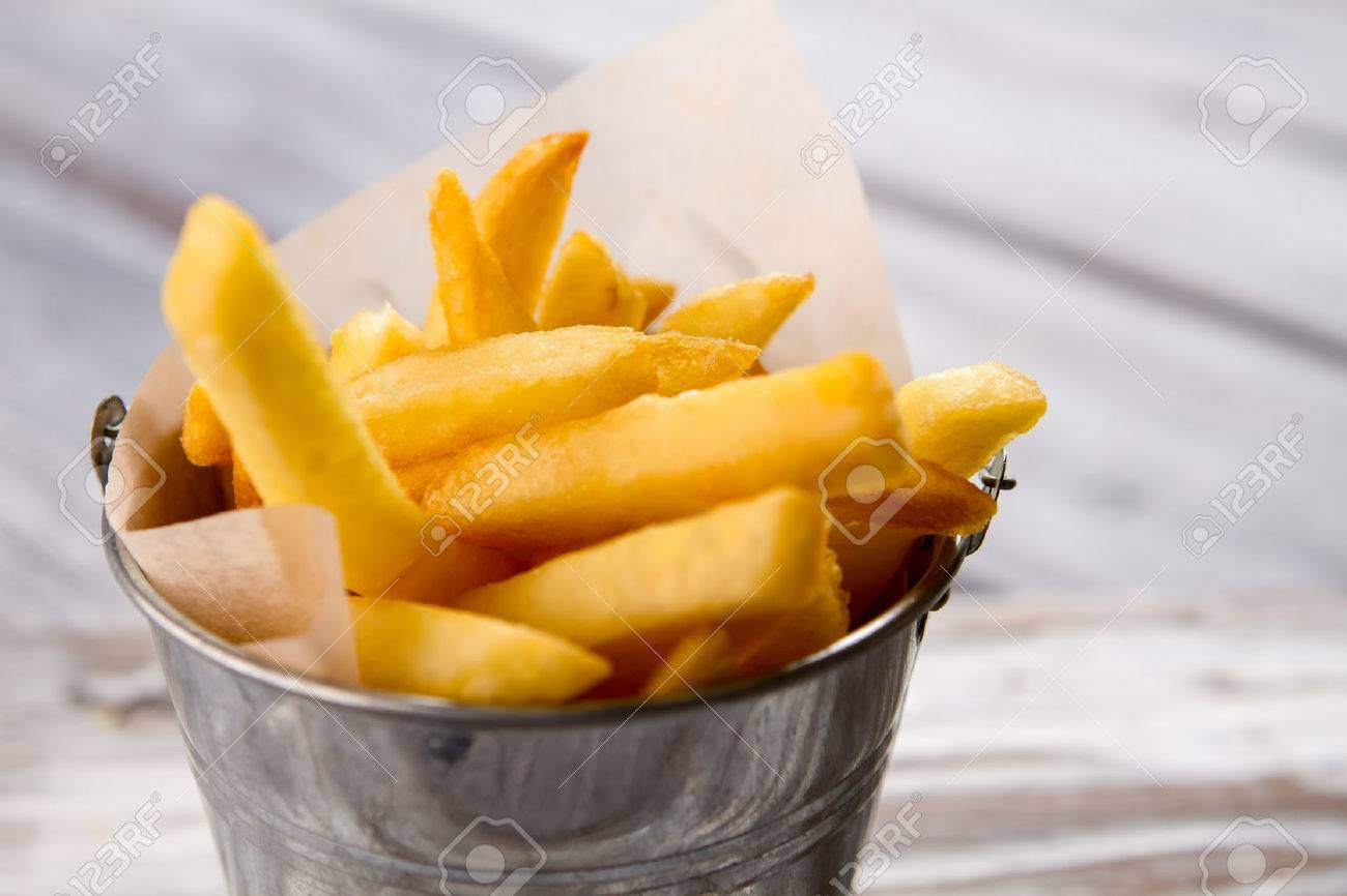 Bucket with yellow fries. - 60327762