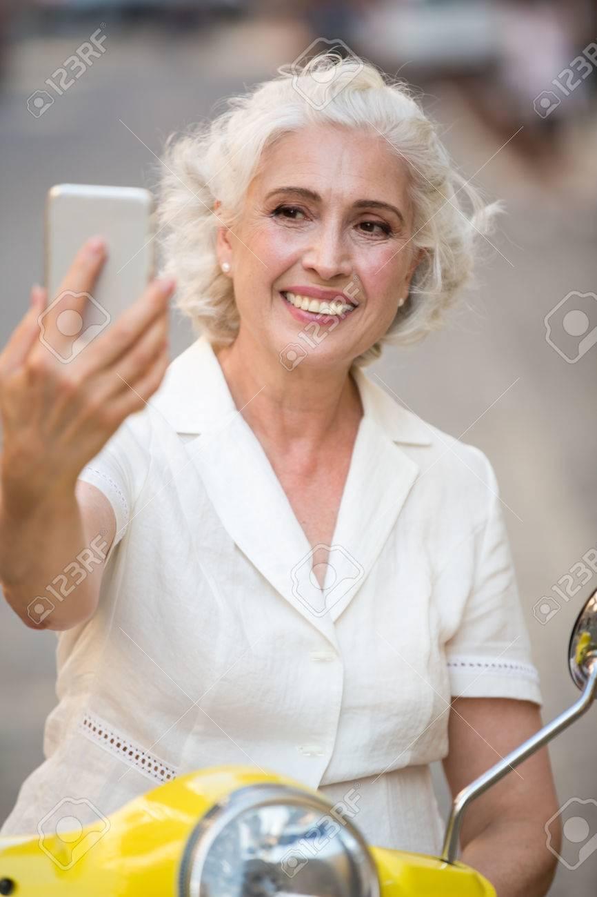 Smiling Dame Schaut Auf Telefon ältere Frau Mit Glücklichem Gesicht