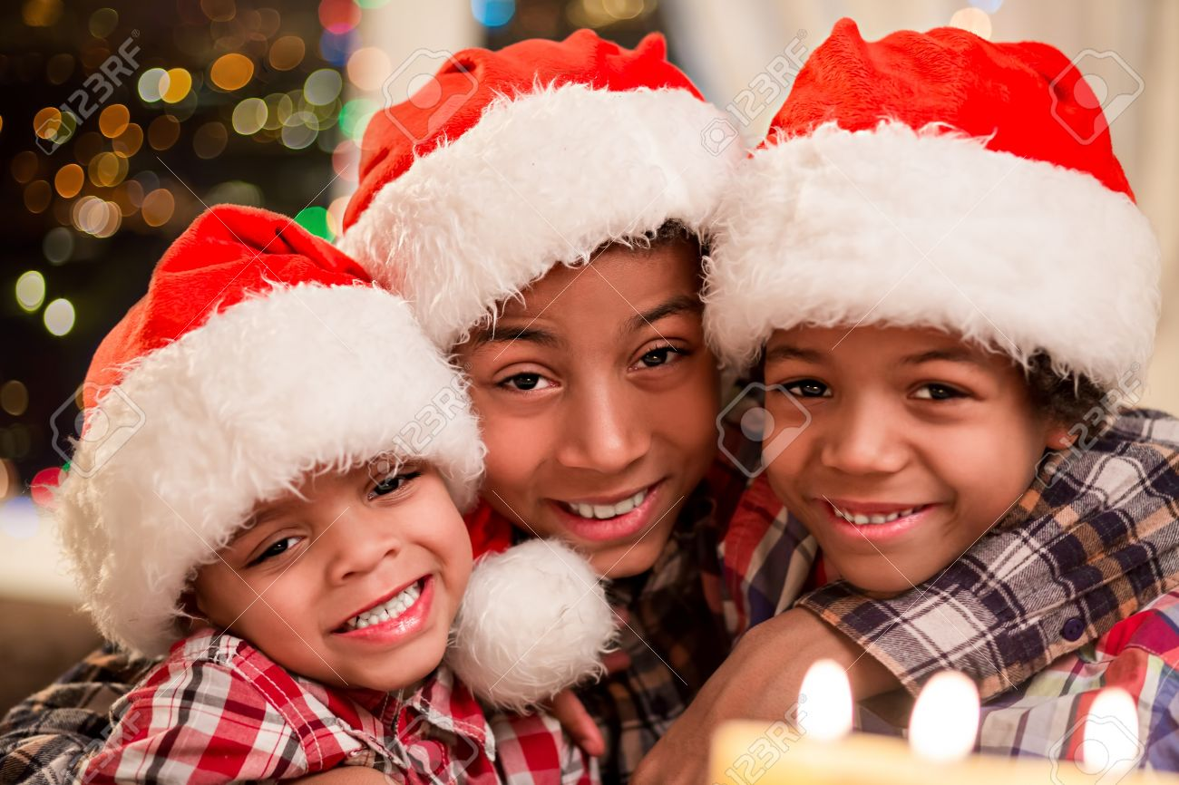 Christmas Hats For Kids.Three Kids In Christmas Hats Smiling Afro Boys On Christmas