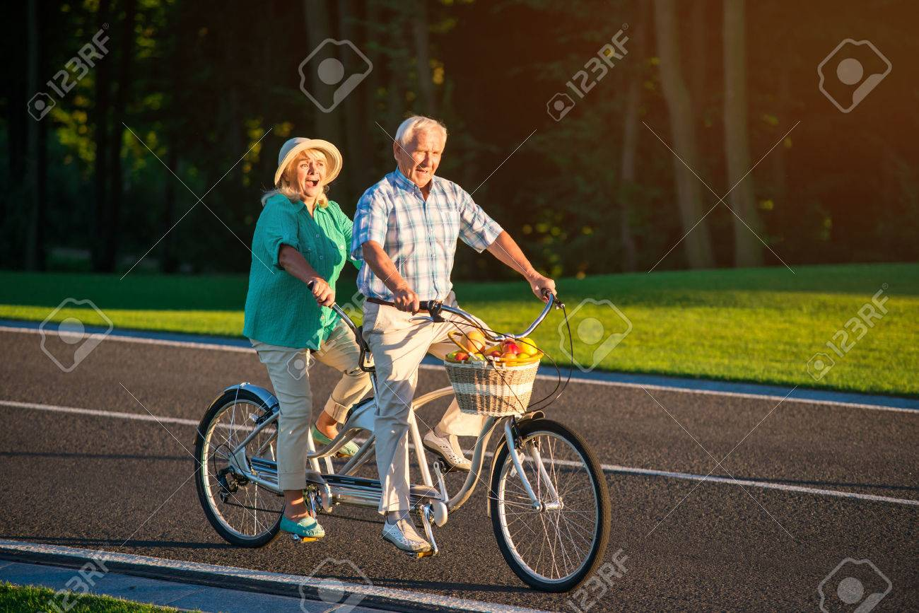 Senior Couple Riding Tandem Bike People Ride On The Road Spin Pedals Faster