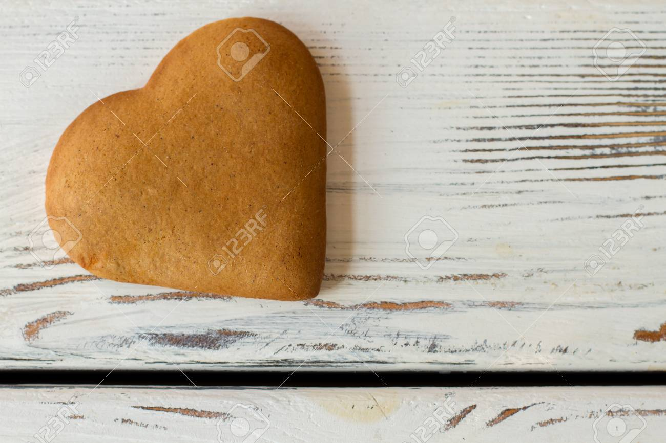 Brown heart shaped cookie biscuit on white wooden surface send brown heart shaped cookie biscuit on white wooden surface send greetings to beloved person m4hsunfo