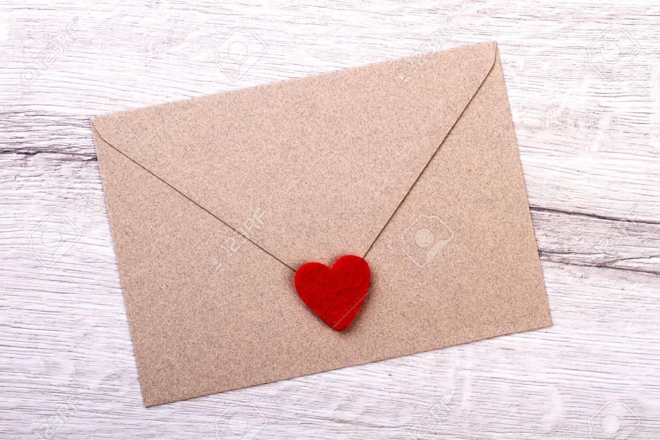 Corazón De La Tela En El Sobre Carta Sobre La Superficie De Madera