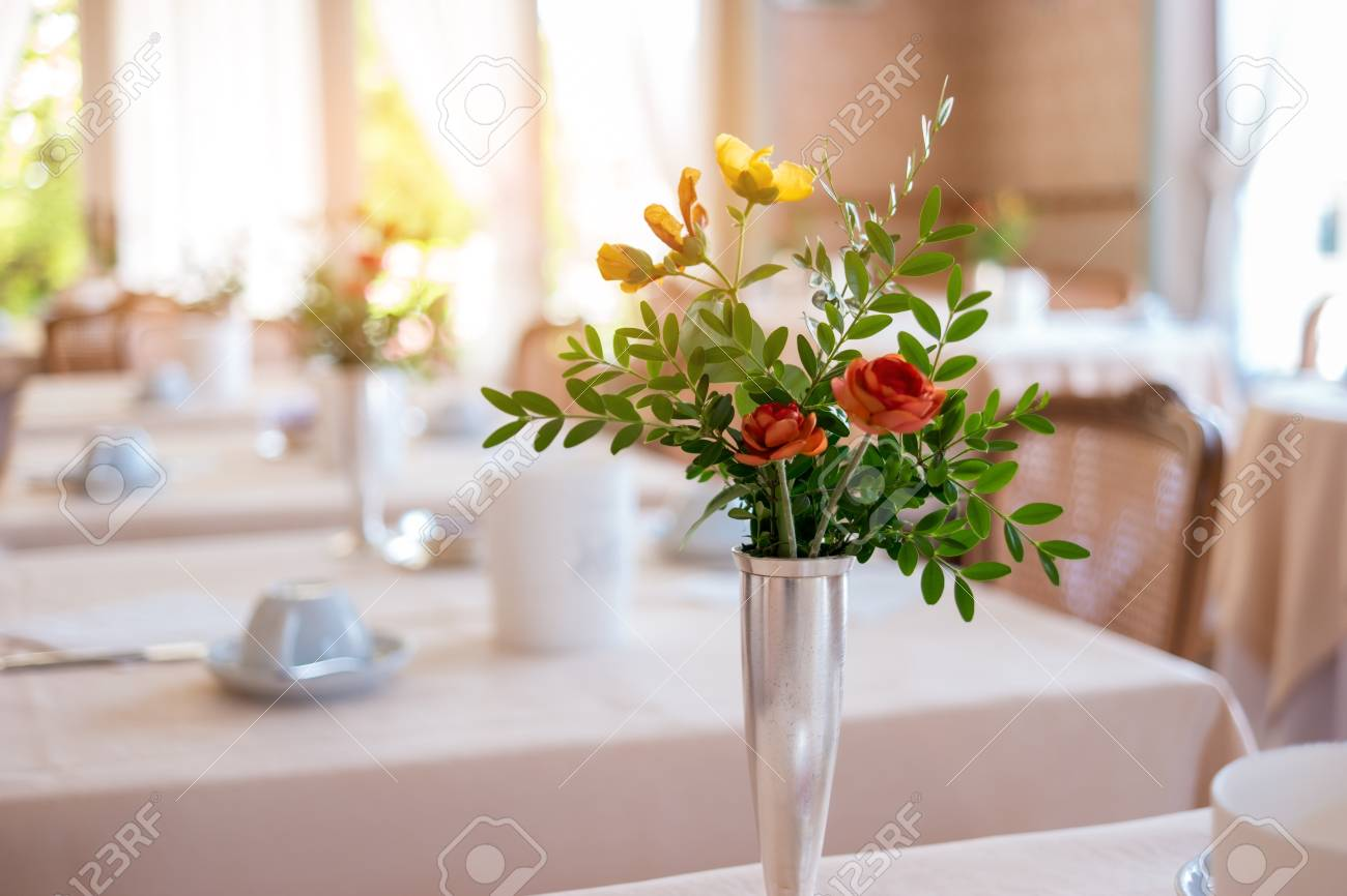 123RF.com & Vase with flowers and leaves. Blurred dining tables. Tasty food..