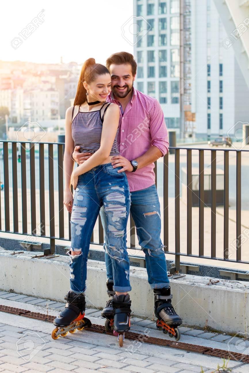 Waren Jung Und Frei Smiling Paar Auf Inline Skates Leute Die Auf Stadtischen Hintergrund Waren Jung