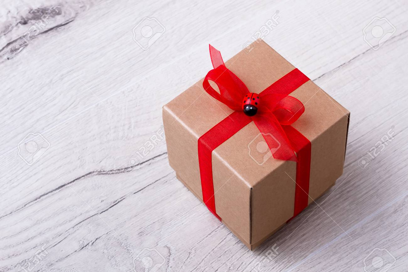 Gift Box On Wooden Plank Red Ribbon On Present Box Decorate
