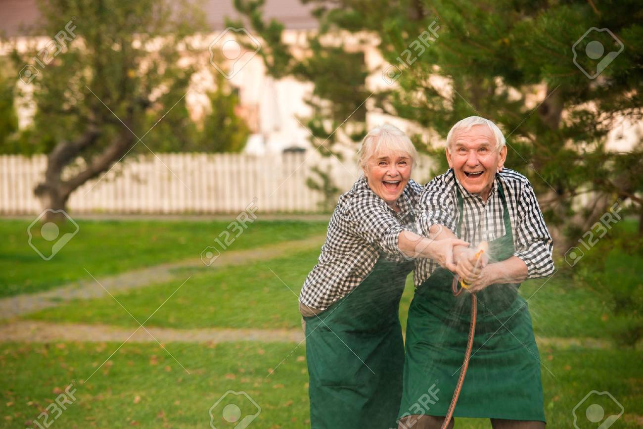 Old couple having fun. Happy people with garden hose. - 81343652