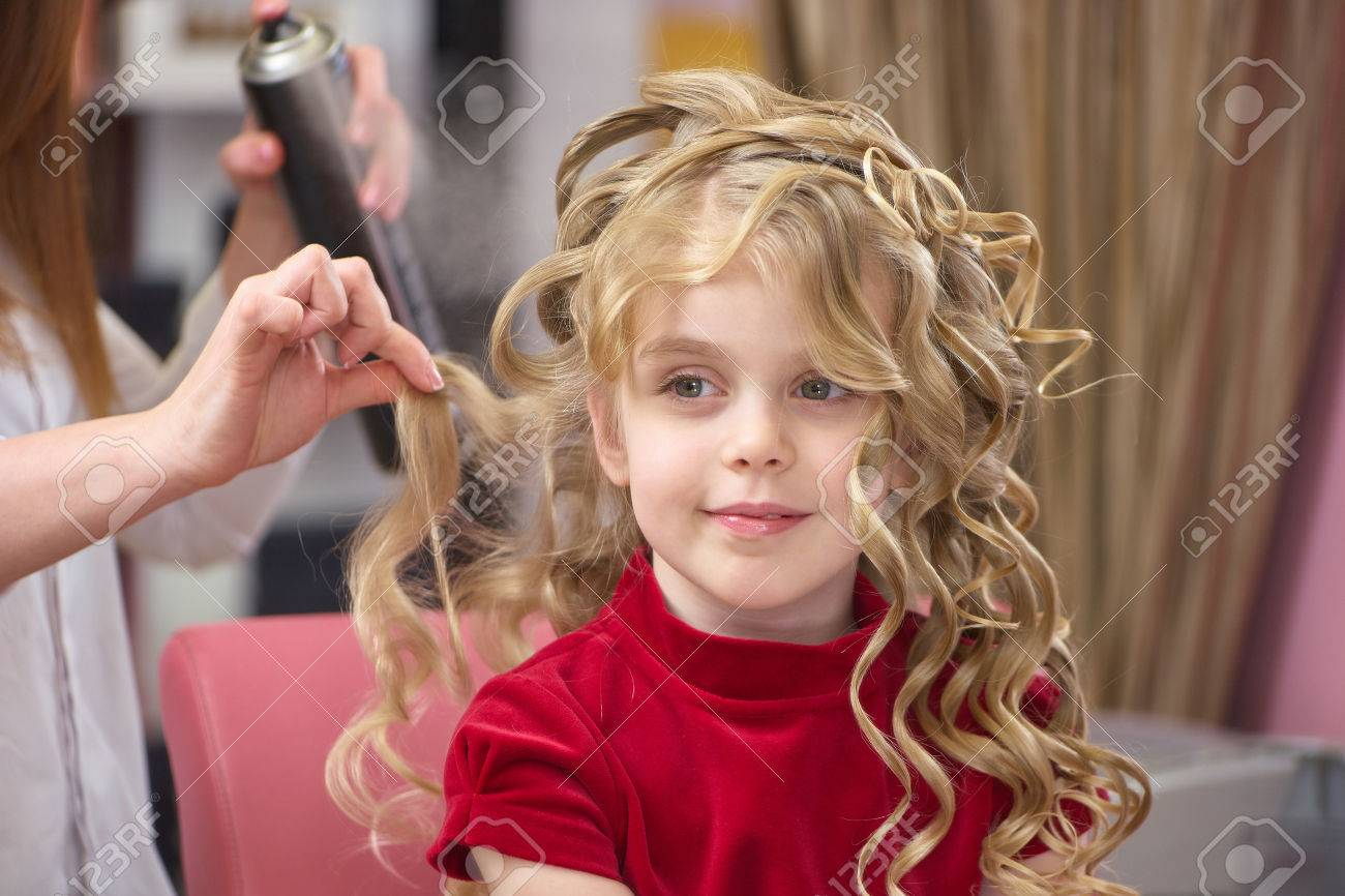Little Girl With Curly Hair Kid At The Hairdresser Stock Photo