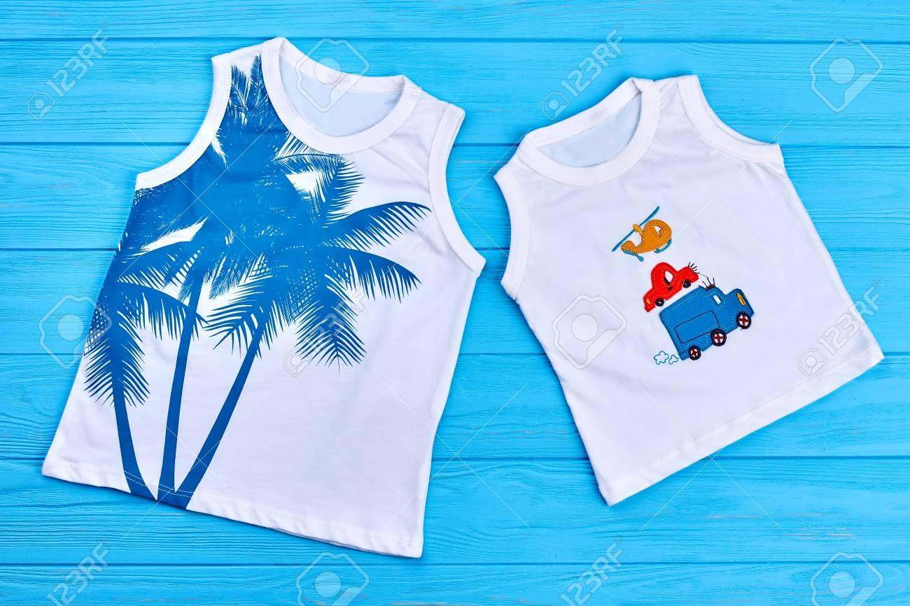 e1a981d09 Niños y niñas camisetas de moda. Camisetas impresas orgánicas de los niños,  fondo de madera azul. Ropa de verano para niños con estampado de ...