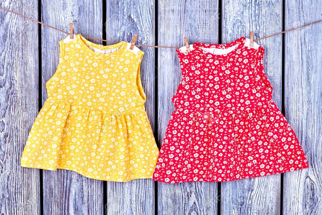 84cb267fc5a4 Kids dresses hanging on rope. Baby-girl apparel drying on clothesline