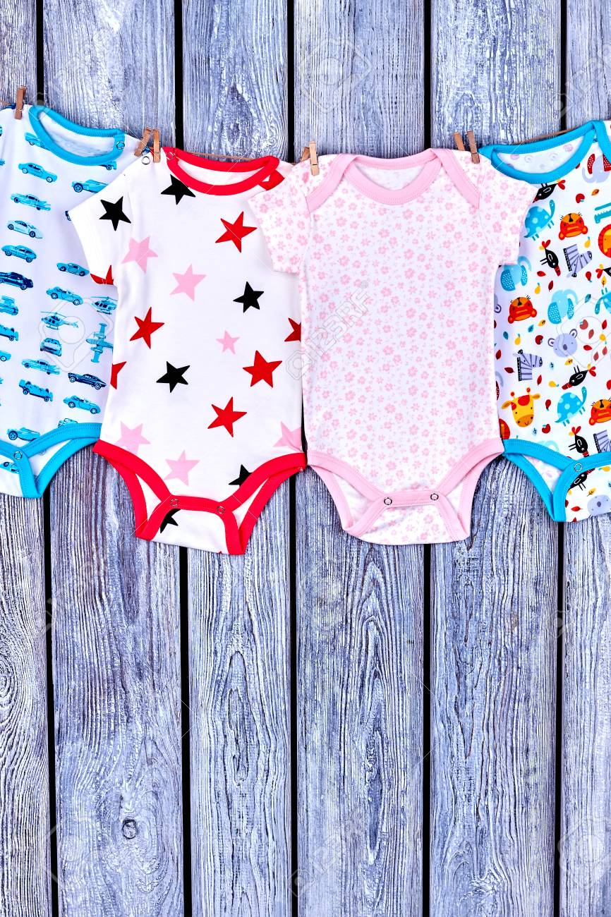67e571a45e2a Kids washed clothes on rope. Infants summer rompers hanging on clothesline  on grey wooden background