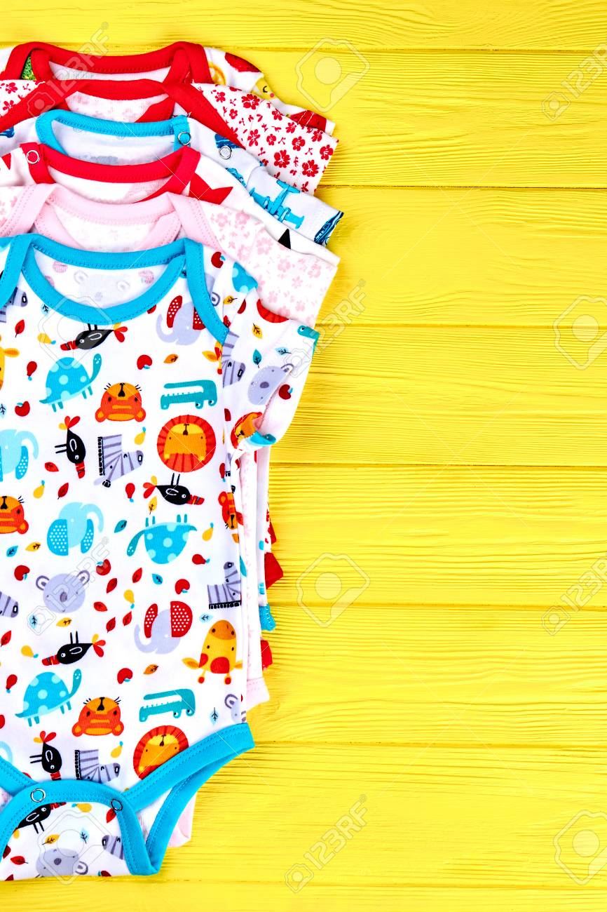dd2f3a5d7 Set of babies soft rompers. Newborn kids boutique clothes on yellow wooden  background, top