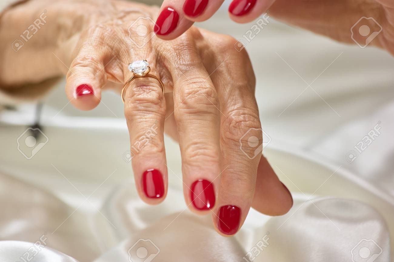 Female Finger Indicating On Diamond. Senior Woman With Red Nails ...