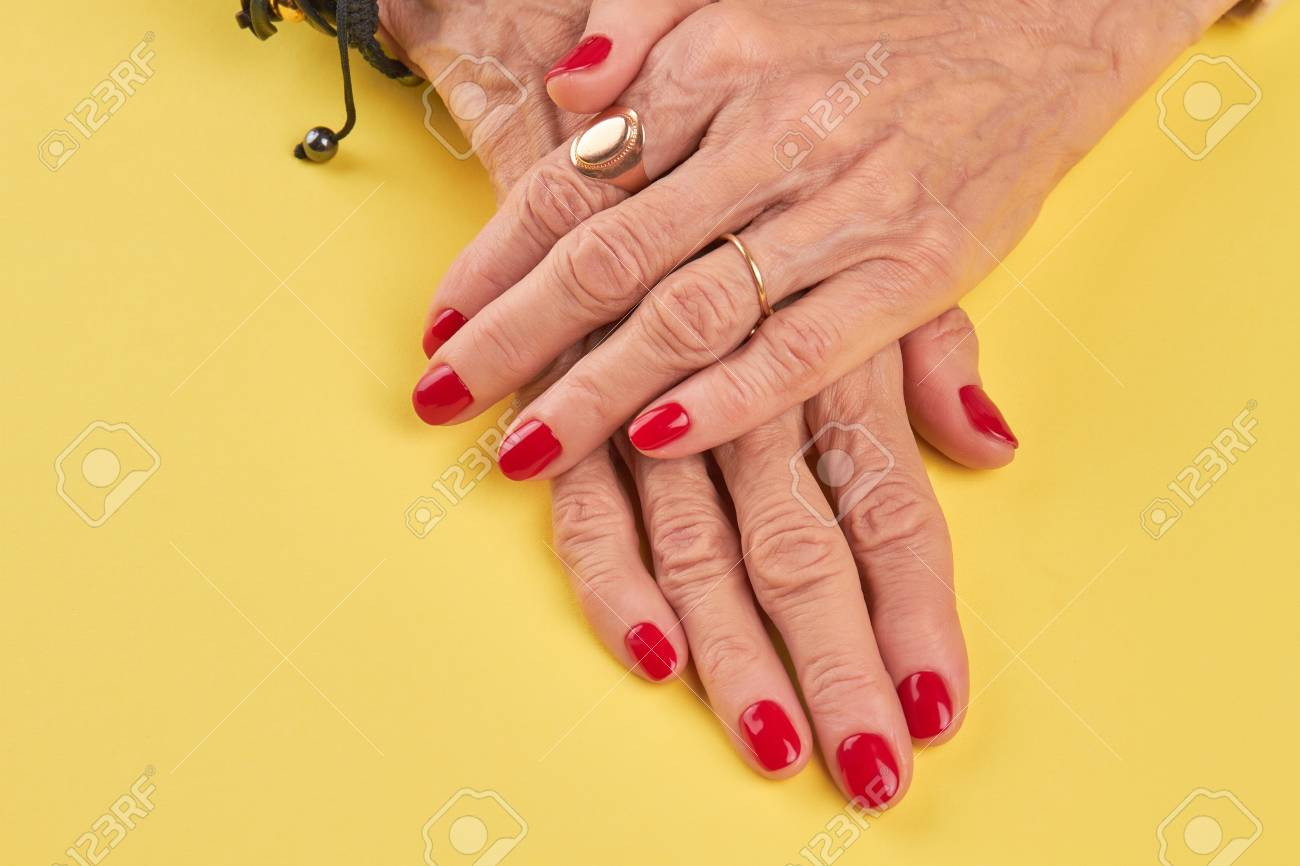 Female Hands With Beautiful Red Manicure Senior Woman Nails Polish On Yellow