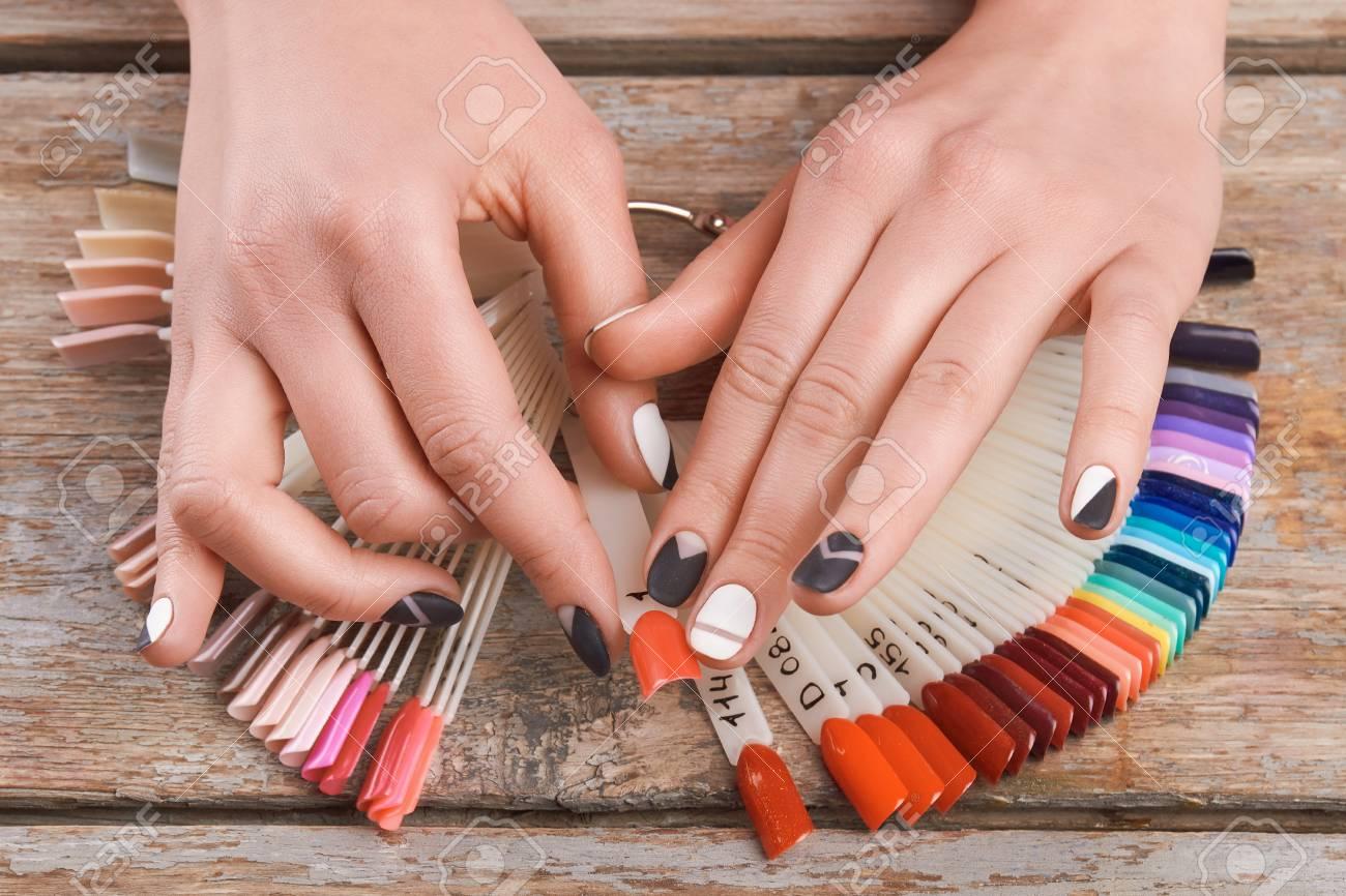 Female hands choose peach cnail color. Woman hands holding color..