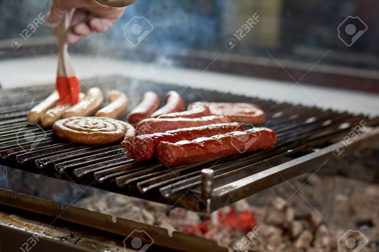 bbq with sausages on the grill. chef cooking different sausages