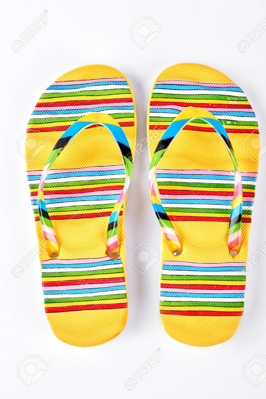 5a49654c0 Stock Photo - Summer fashion striped slippers. Yellow flip flops in colorful  stripes isolated on white background. Fashion beach footwear.