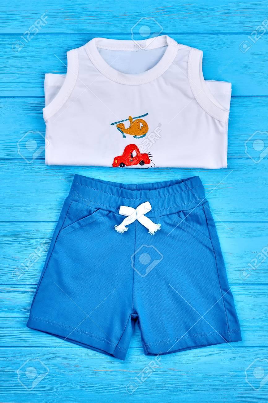 f87ab1d3b6eeb Banque d'images - Costume d'été en coton bébé garçon. Vêtements de garçon  nouveau-né sur un fond en bois bleu.