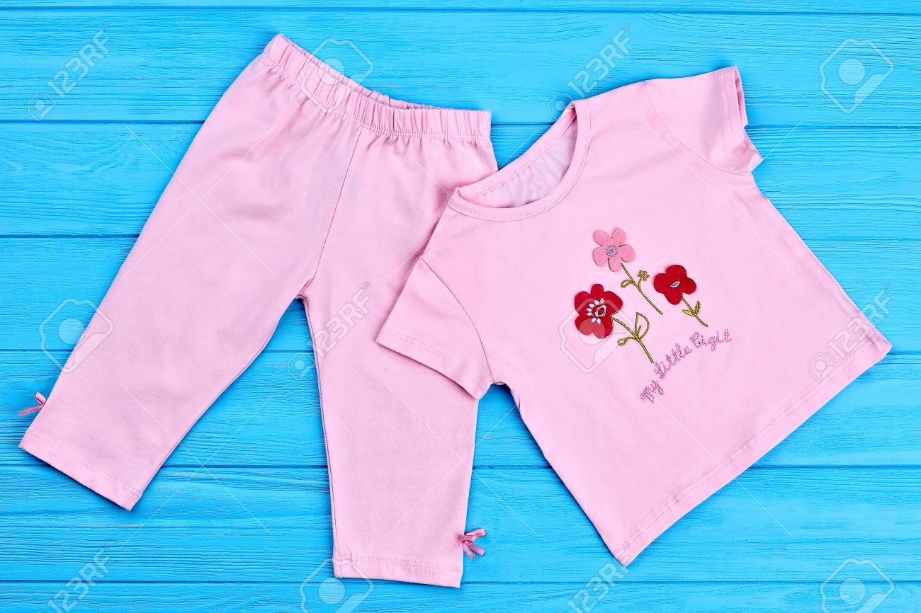 54d7e7d79 Beautiful baby-girl cotton suit. Summer children natural pink suit on blue  wooden background