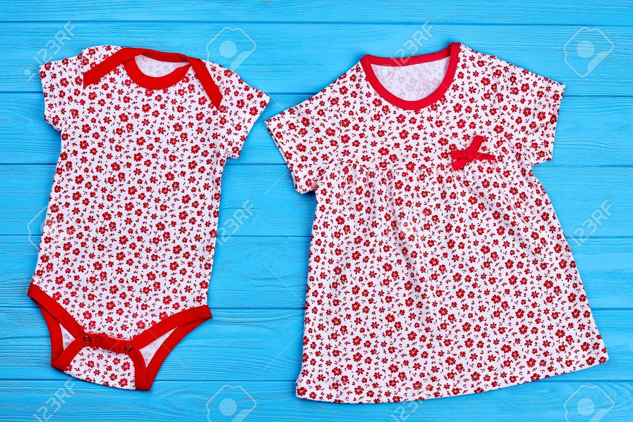 28db86ab940 Stock Photo - Toddler girl cotton summer garment. Small red flower print  bodysuit and dress for baby girl on wooden background