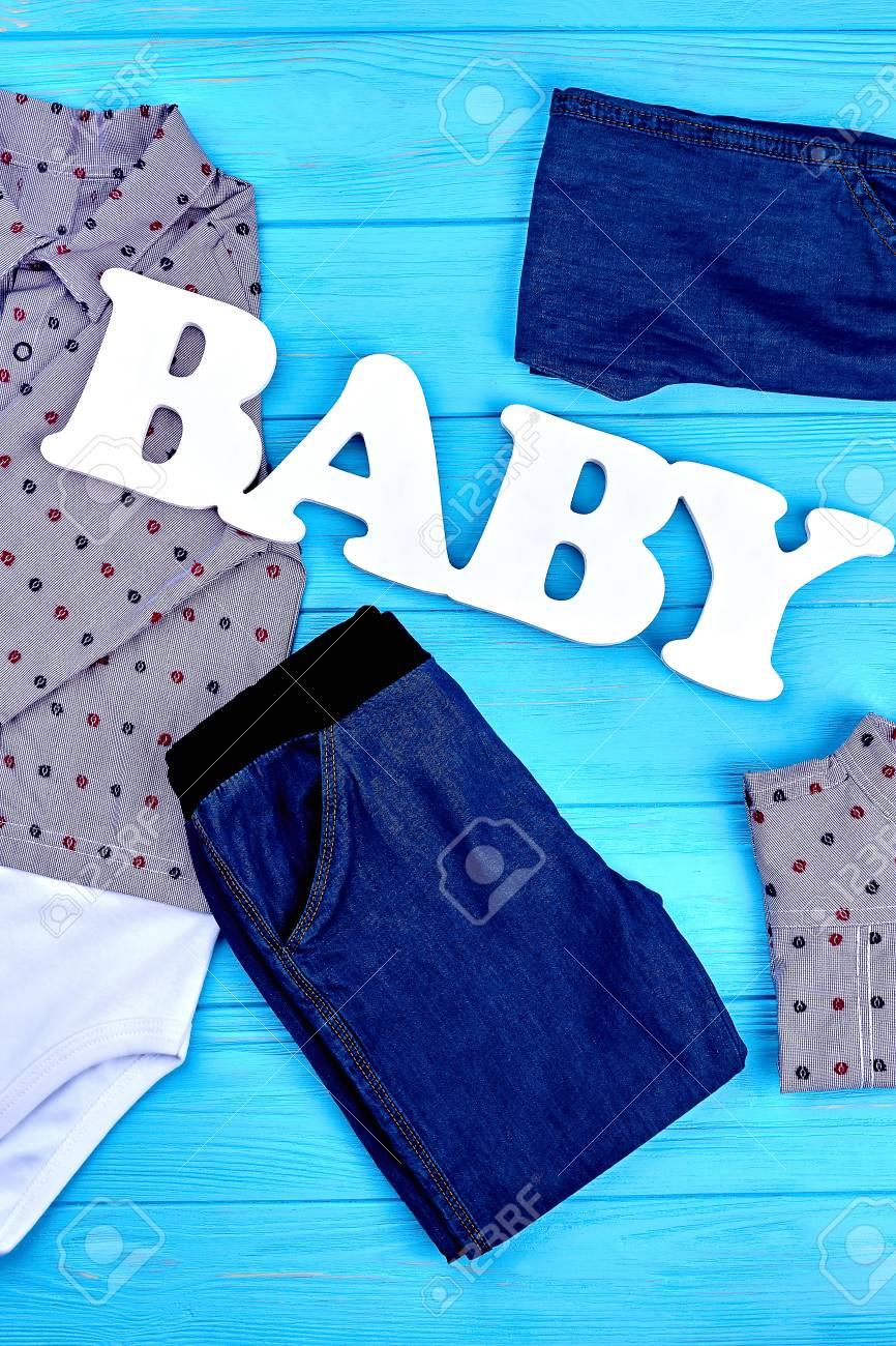 ae77dc034e2e3 Collection De Vêtements De Marque Pour Bébés. Ensemble De Nouveaux Vêtements  De Jean Pour Bébé Garçon Sur Un Fond En Bois Bleu