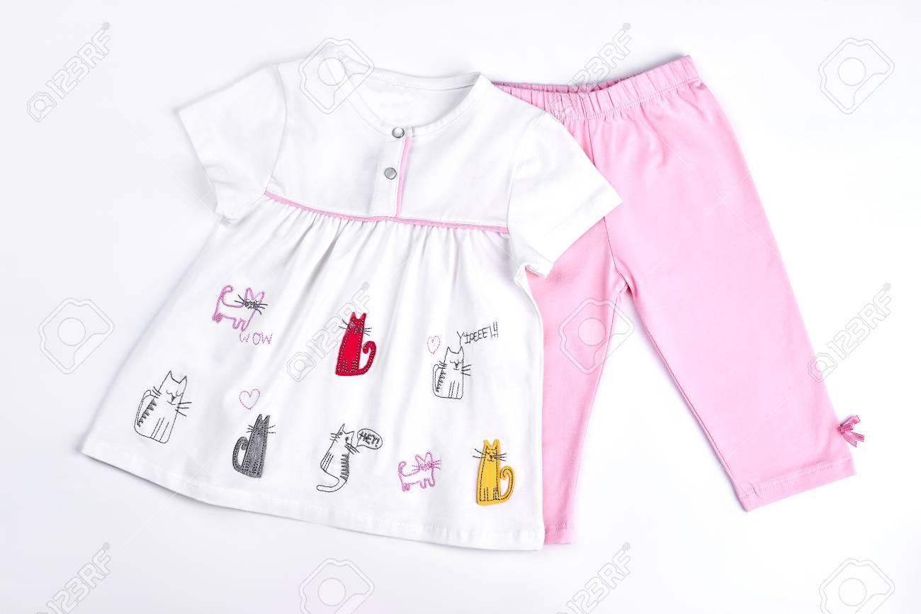 52557583dd2 Foto de archivo - Ropa de verano hermosa niña recién nacida. Conjunto  infantil de dibujos animados blanco vestido y polainas de color rosa.