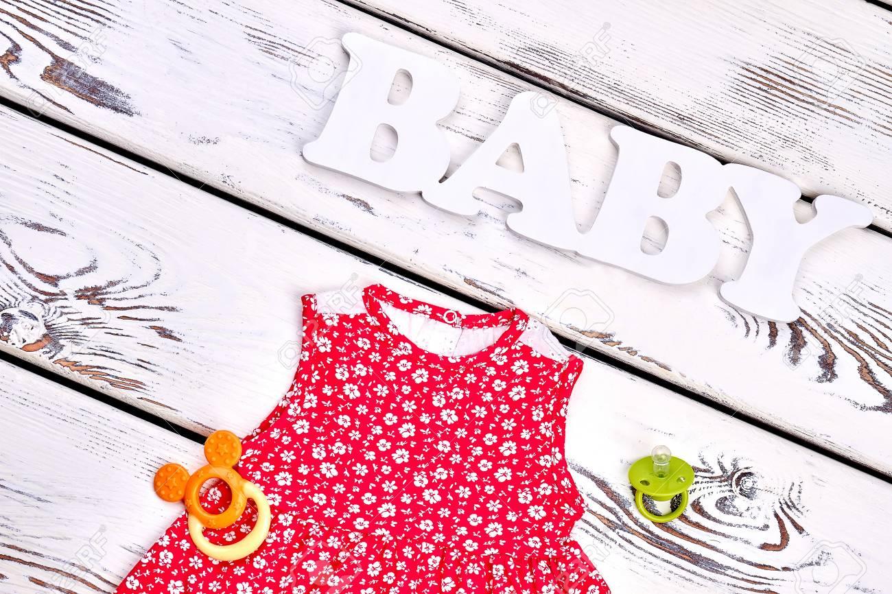 Vestido Estampado Bebe Niña Accesorios Bebé Del Texto Vestido Modelado Rojo Del Algodón De Los Niños Mordedor Pacificador En Fondo De Madera Del