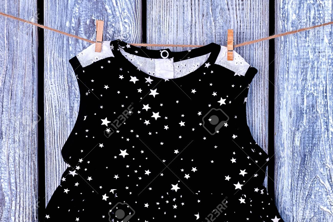 bf3b86621d19 Baby clean top hanging on rope. Infant girl black patterned dress drying on  clothesline on