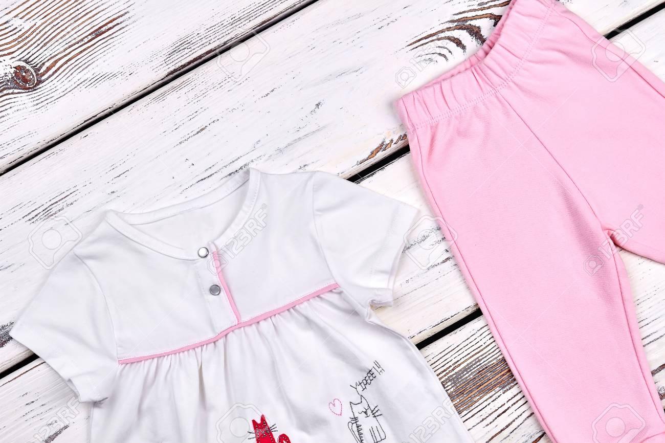 d7bf10743 Foto de archivo - Traje de algodón lindo de niña pequeña. Top blanco hermoso  de la niña infantil y pantalones rosados   en fondo de madera. Ropa de  marca ...
