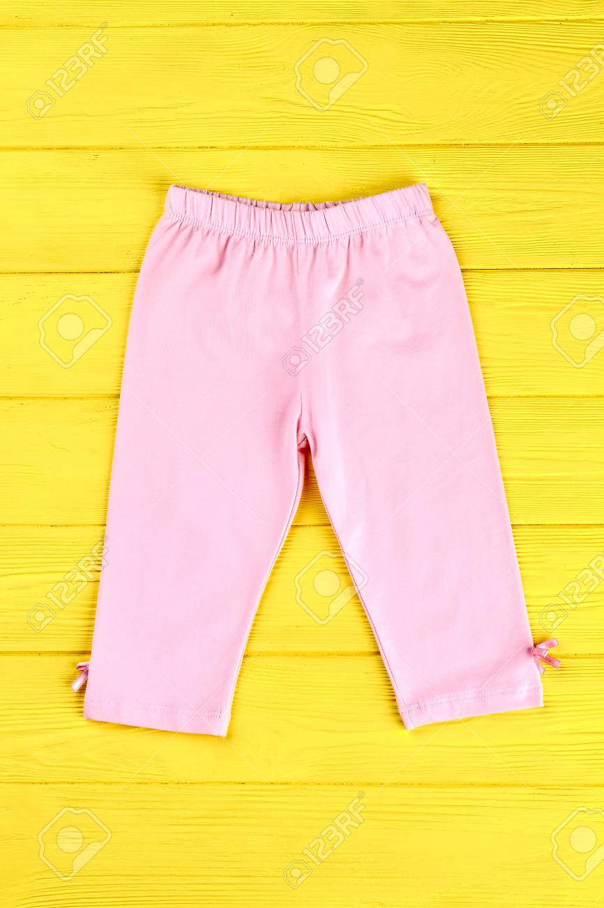 93533498dca8b Babies beautiful pink leggings. Infant girl cute cotton pants on yellow  wooden background. Kids