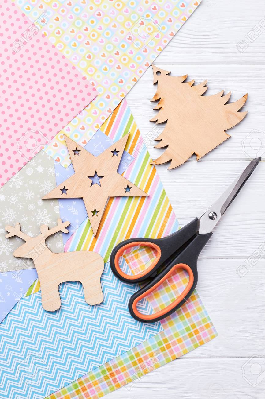 carved wooden christmas ornaments scissors patterned paper sheets scissors cut out christmas