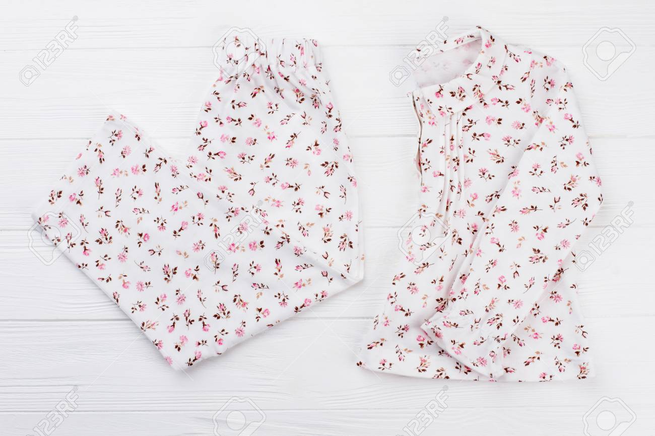 Girls pajama with flower print. Set of white shirt and pants on wooden  background. a7aee08c3