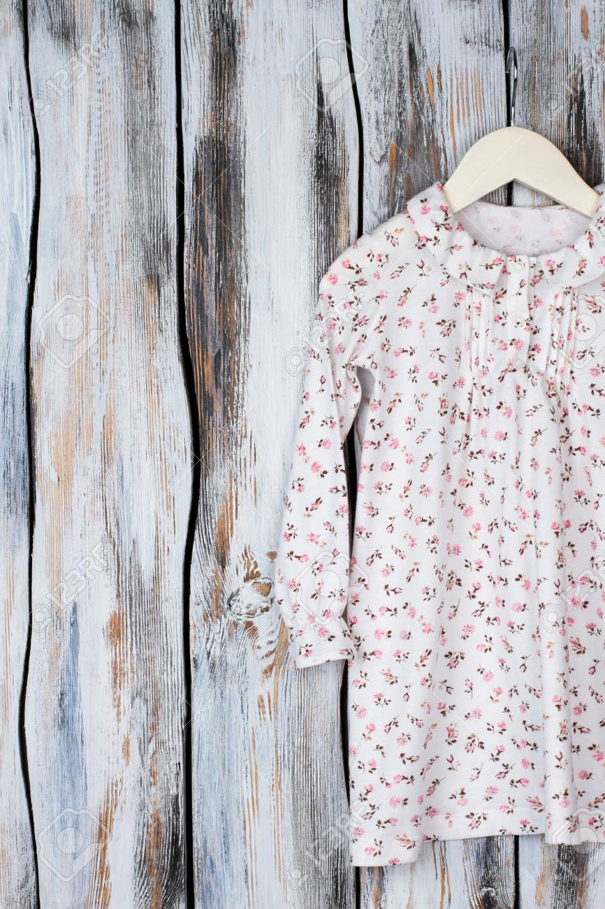 Floral nightgown for young girls on wooden background. Long sleeve and ruffle  collar. Sleeping 34569e6c8