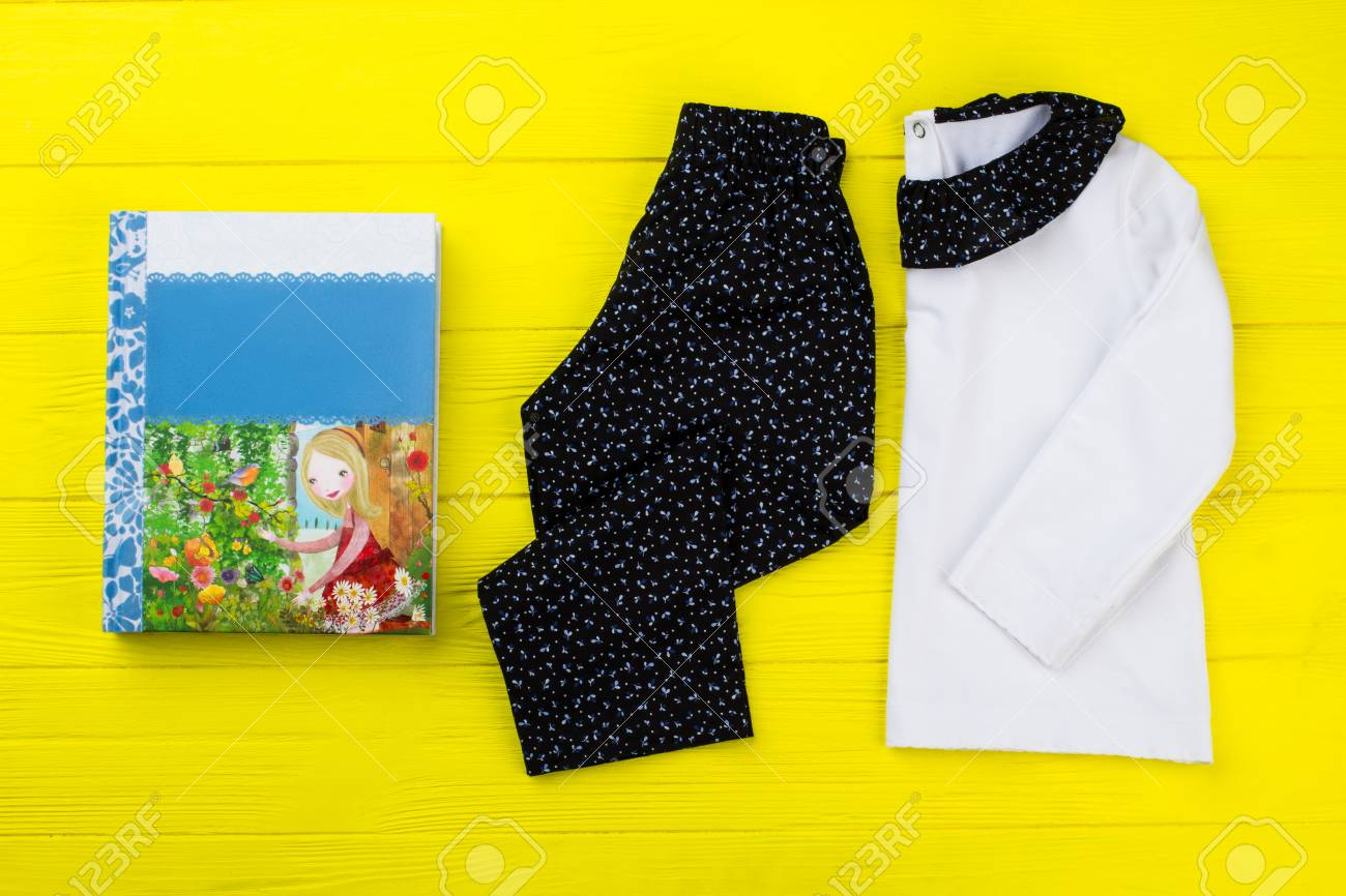 ec7d6827c32a Girls clothes and fairytale book on yellow background. Black and white  pajama set with floral
