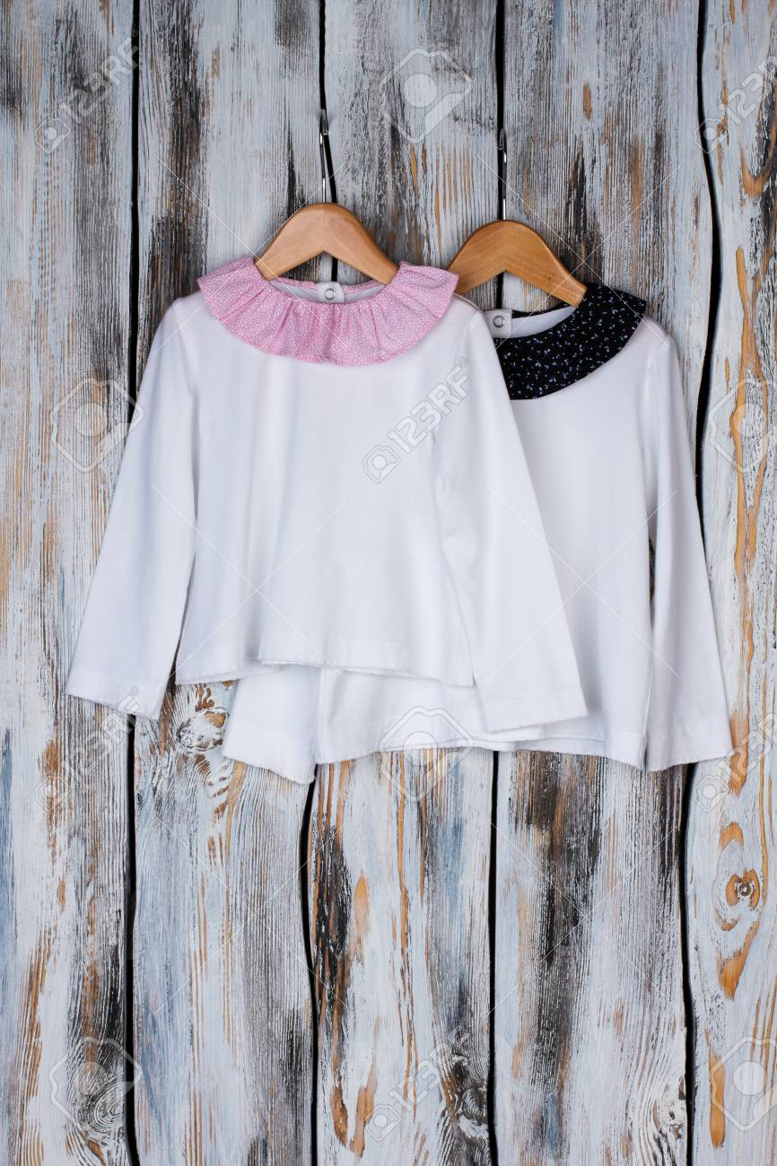 Girls nightwear on wooden hangers over rustic background. Cotton pajama  tops with round collar. c31f185b5