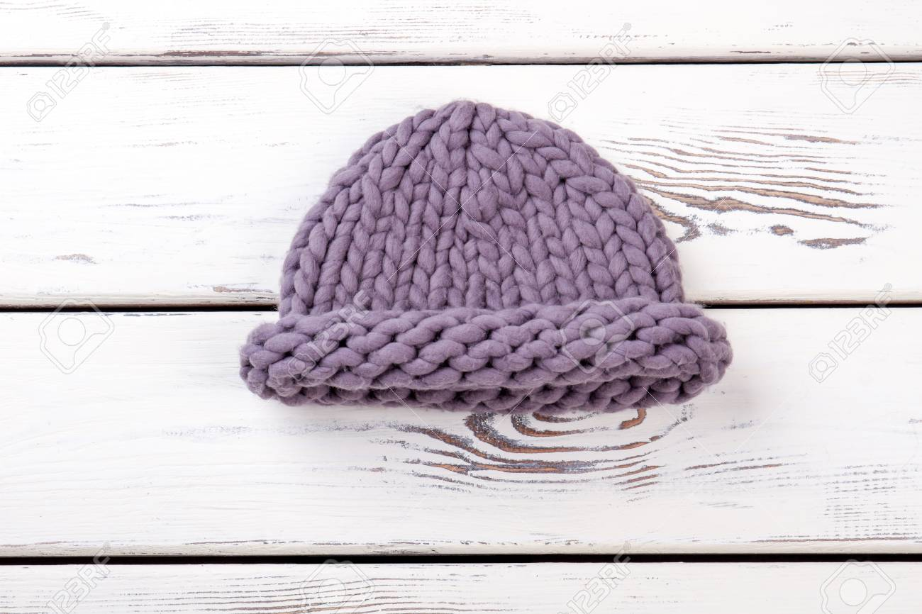 Female merino knitted hat. Women purple color winter hat on white wooden  background. Ladies b287ea35053
