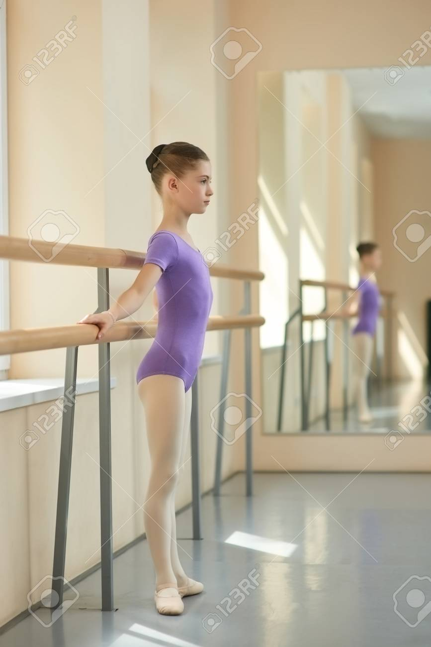 b0fa37f9c37a Girl Standing At Railing In Ballet Hall. Child Stretching Out ...
