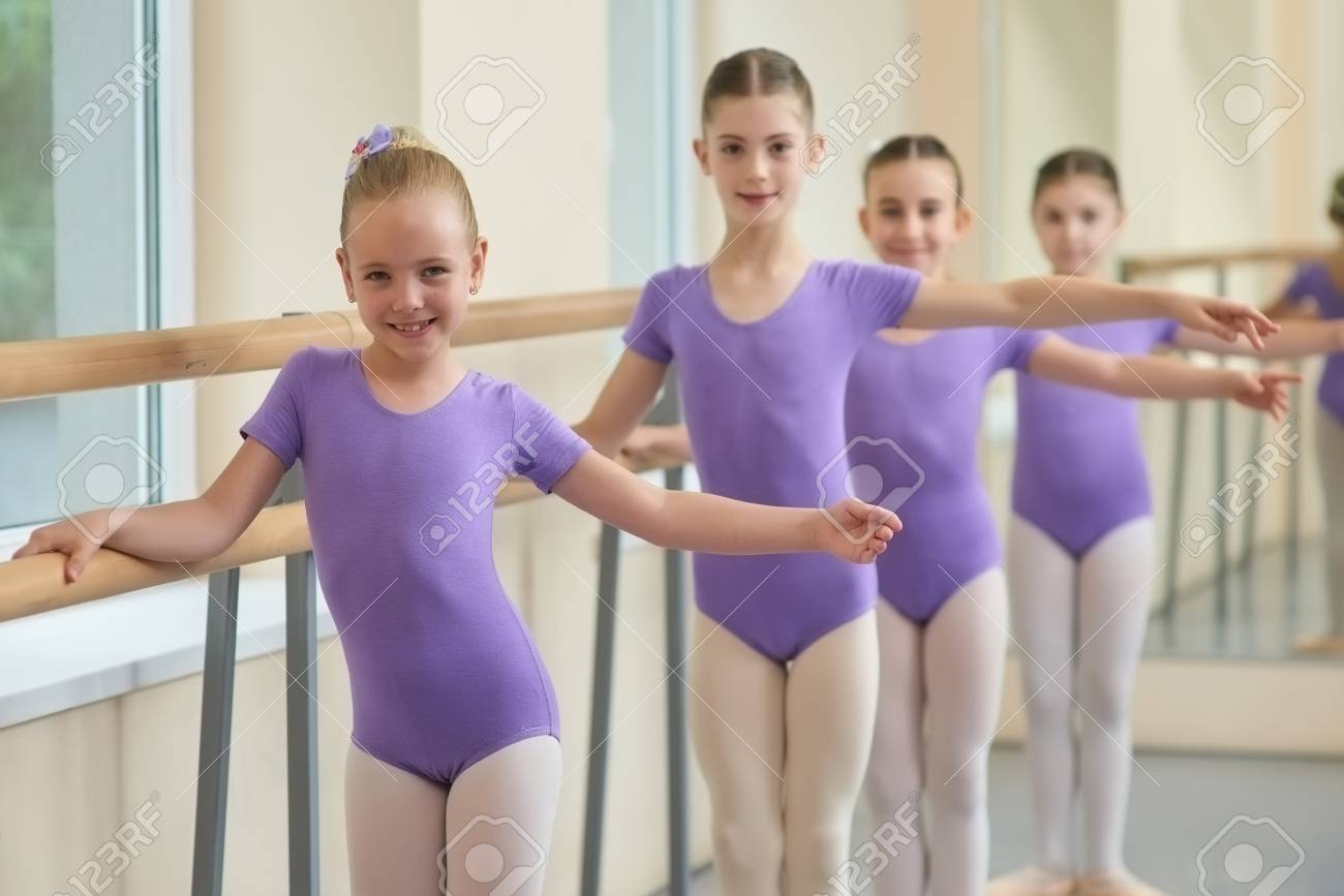 230980bf34d3 Kids Practicing Ballet At Ballet Class. Young Smiling Ballerina ...