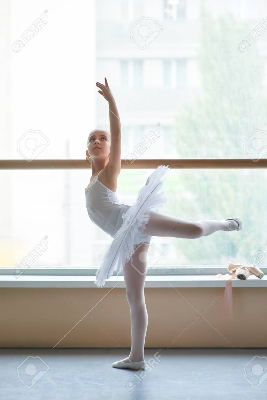 07cd39351fa1 Young Ballerina Practicing Dance Move. Cute Ballet Girl In White ...