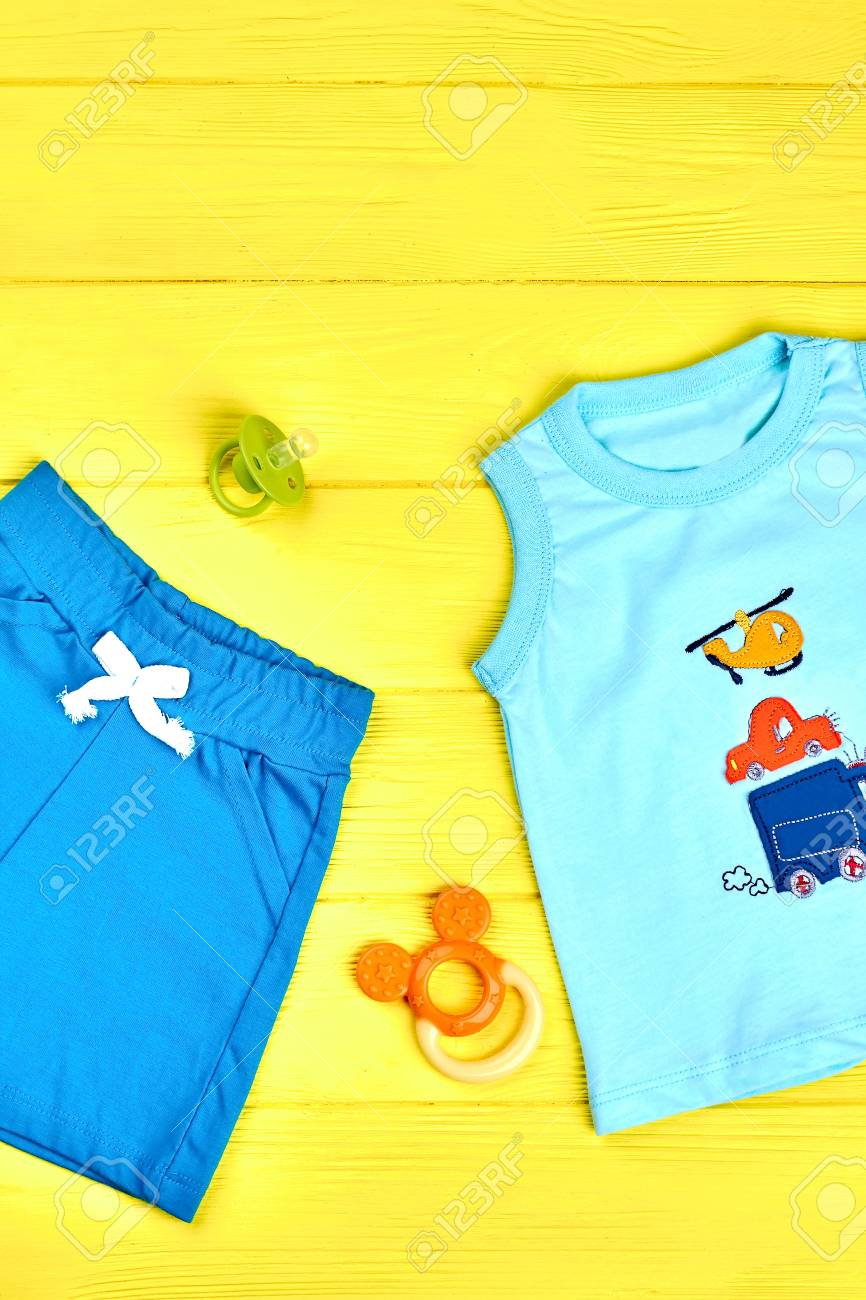 7805aff61 Infant boy summer clothes background. Baby boy cute summer garment,  accessories on yellow wooden