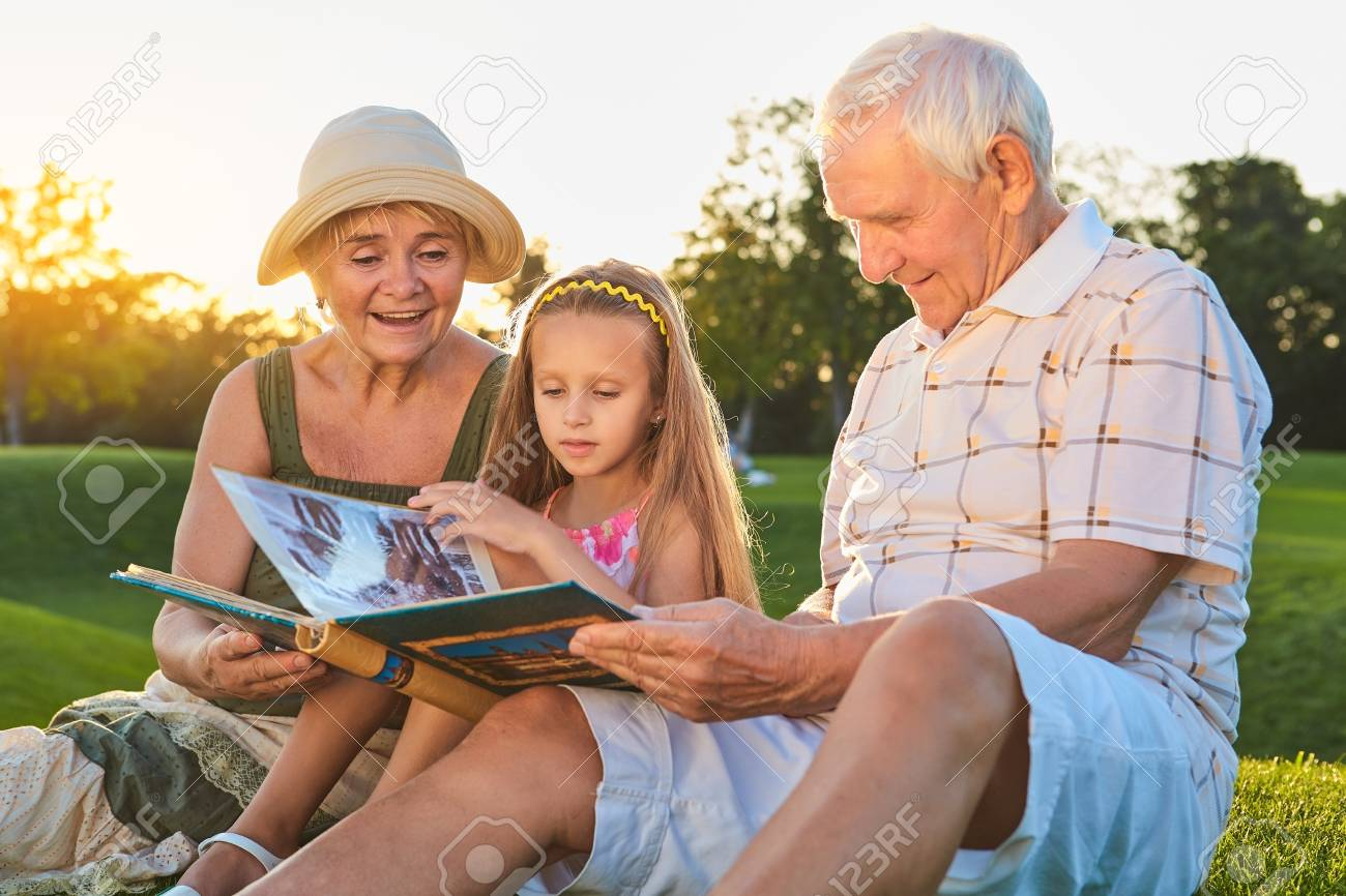 People looking through photo album. Caucasian girl with grandparents outdoors. Pages of the past. - 100540616
