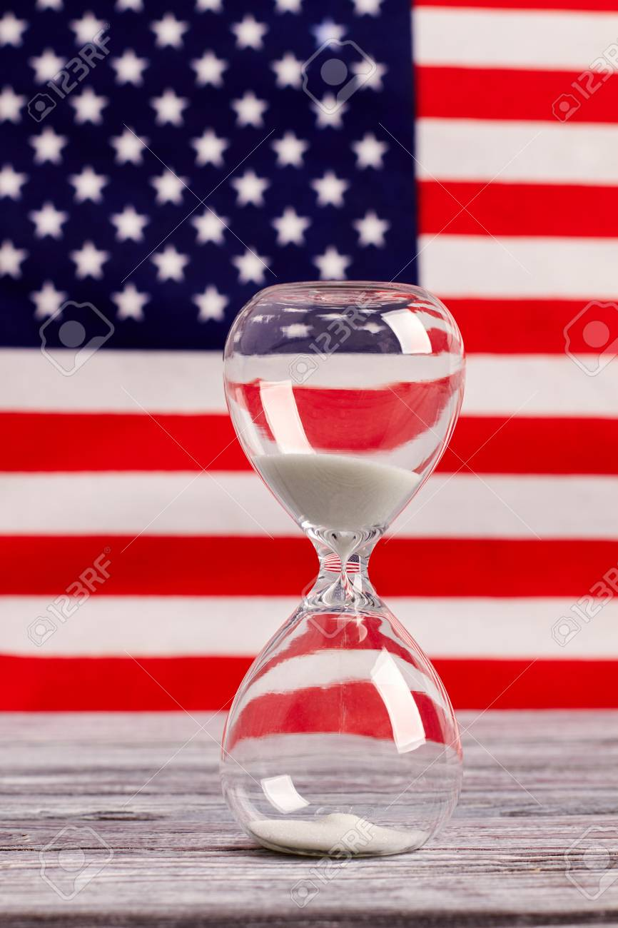 Hourglass On Table With USA Flag In The Background Sand Glass Old Wooden