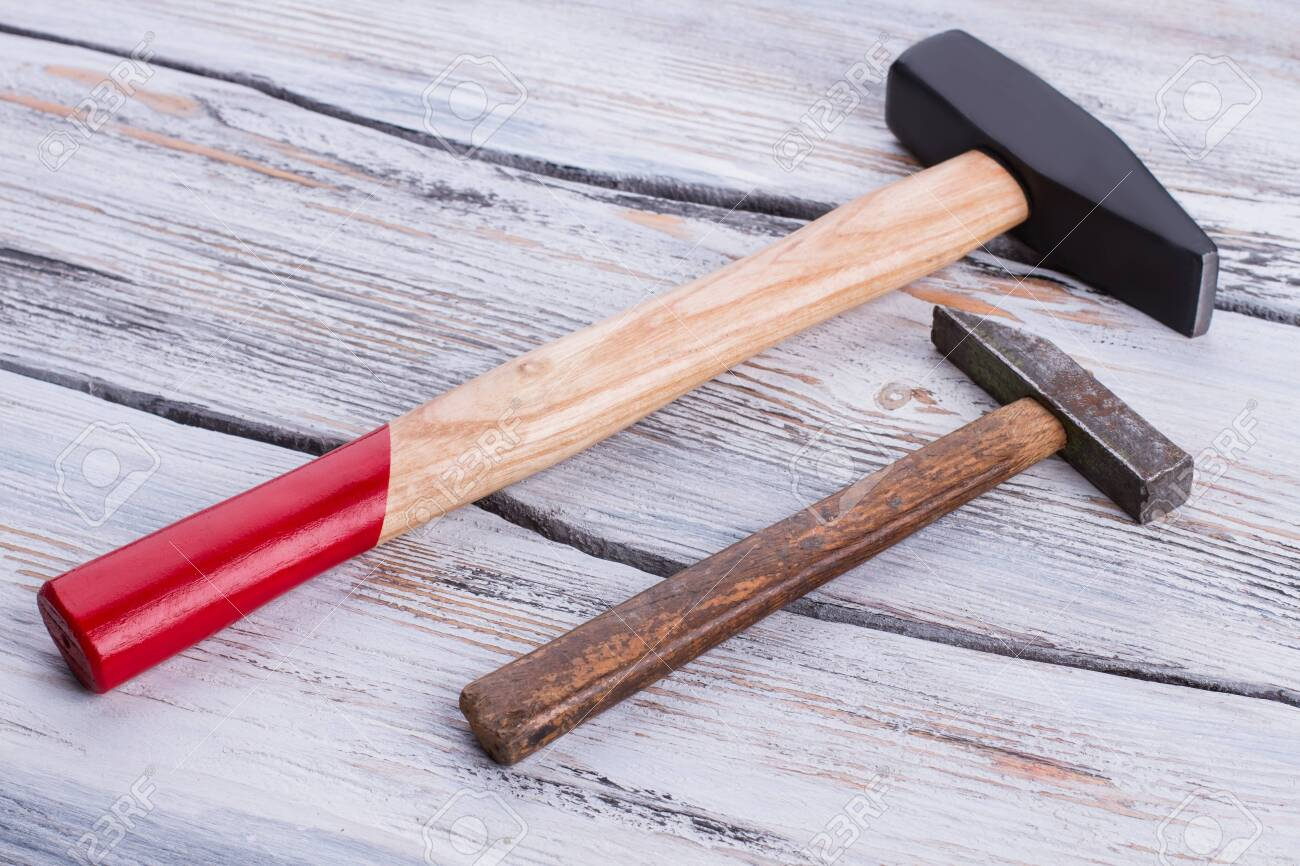 Old and new hammers on wooden background. Hammers with wooden handles on wood surface. - 124519284